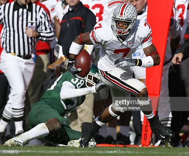 Ted Ginn Jr. #7 of the Ohio State Buckeyes heads up field after breaking the tackle of Kendell Davis-Clark of the Michigan State Spartans during...