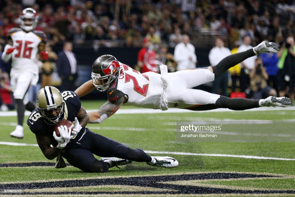 Ted Ginn #19 of the New Orleans Saints catches the ball for a touchdown as Chris Conte #23 of the Tampa Bay Buccaneers defends during the second half of a game at Mercedes-Benz Superdome on November 5, 2017 in New Orleans, Louisiana.