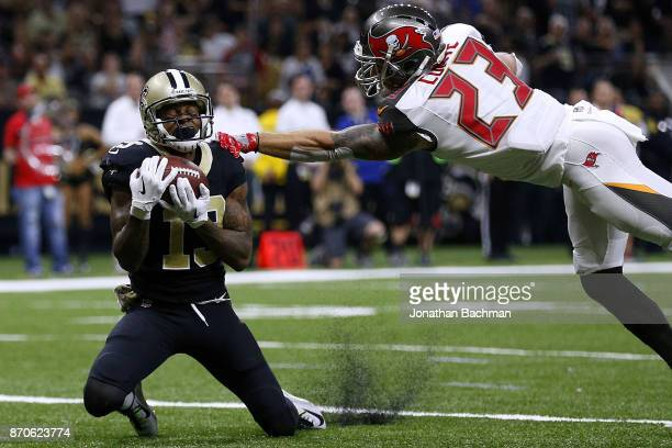 Ted Ginn of the New Orleans Saints catches the ball for a touchdown as Chris Conte of the Tampa Bay Buccaneers defends during the second half of a...