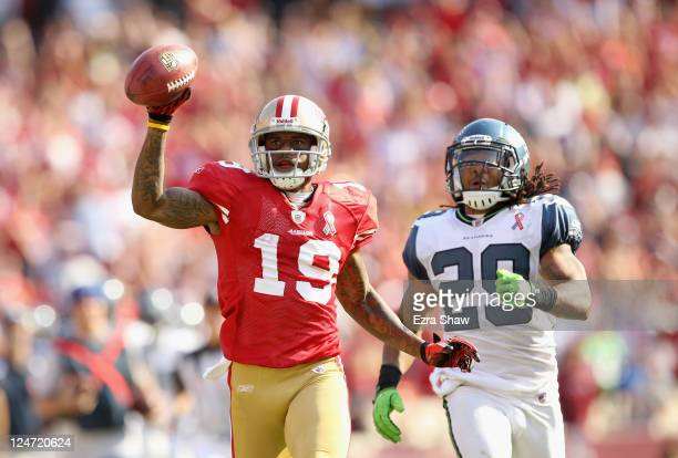 Ted Ginn of the San Francisco 49ers outruns Earl Thomas of the Seattle Seahawks on his way to scoring a touchdown on a kickoff return during their...