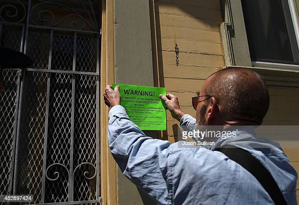 Ted Gullicksen with the San Francisco Tenany Union hangs a sign on a the exterior of a building during a demonstration outside of an apartment...