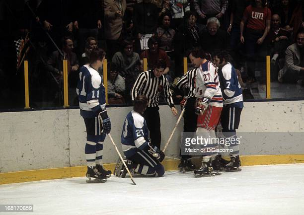 Ted Irvine of the New York Rangers looks down at Eddie Shack of the Pittsburgh Penguins as Shack's teammates Nick Harbaruk and Bryan Hextall talk to...