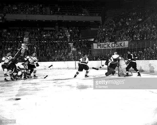Ted Lindsay of the Detroit Red Wings tries to score in front of the New York Rangers net as the goalie takes a puck in the face during an NHL game...