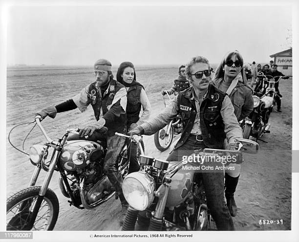 Ted Markland and Tom Sternwith riding motocycles with Suzy Walters and Arlene Martel sitting behind them in a scene from the film 'Angels from Hell'...