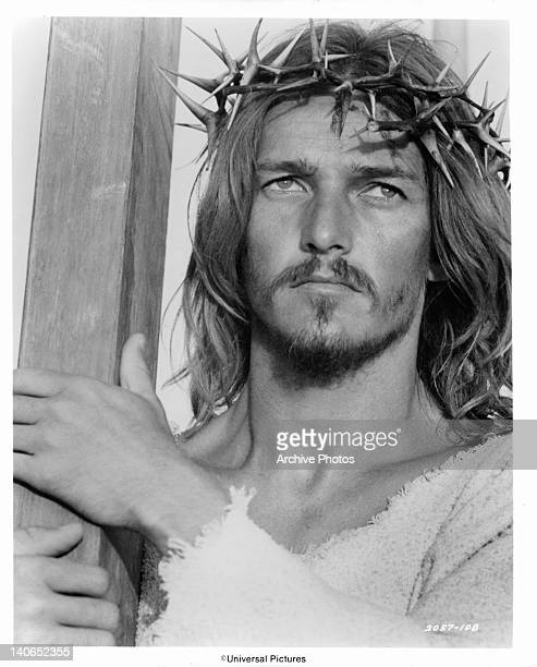 Ted Neeley with a crown of thorns on his head carries the cross to which Roman soldiers will crucify him in a scene from the film 'Jesus Christ...