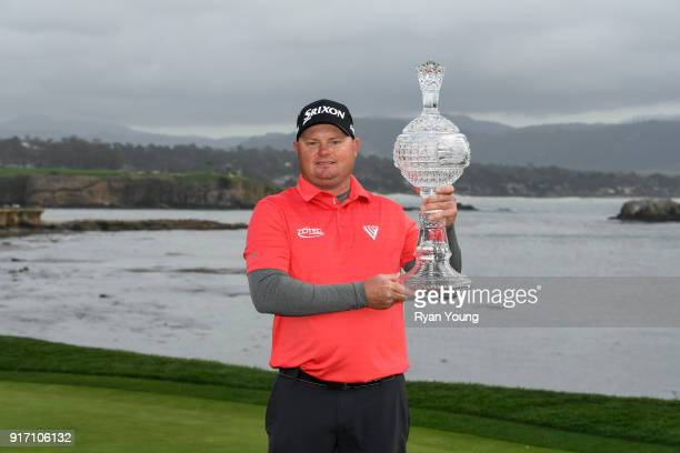 Ted Potter Jr poses for photographs with the trophy following the final round of the ATT Pebble Beach ProAm at Pebble Beach Golf Links on February 11...
