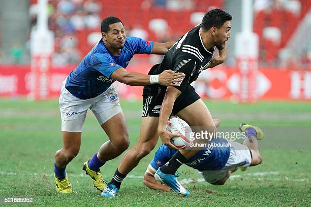 Ted Stanaway of New Zealand is tackled Ed Fidow of Samoa during the 2016 Singapore Sevens Plate Final between New Zealand and Samoa at National...