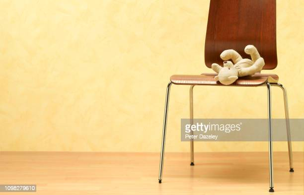 teddy abandoned on chair of waiting room - fragility stock pictures, royalty-free photos & images