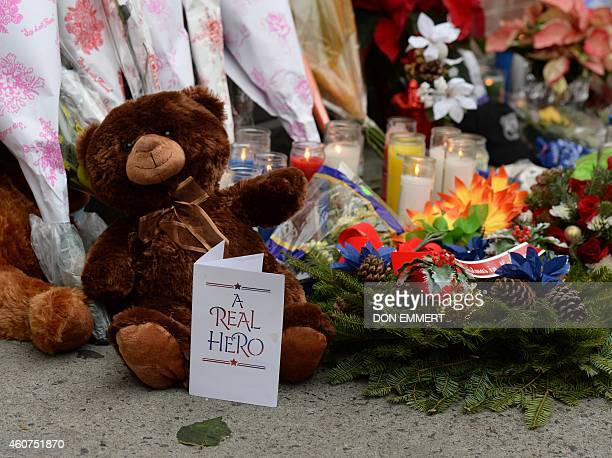 A teddy bear and a card are left at a memorial near Tompkins Ave and Myrtle Ave December 21 2014 in New York near the site where two New York City...