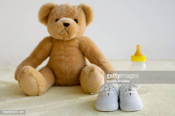 Teddy bear, baby shoes and bottle