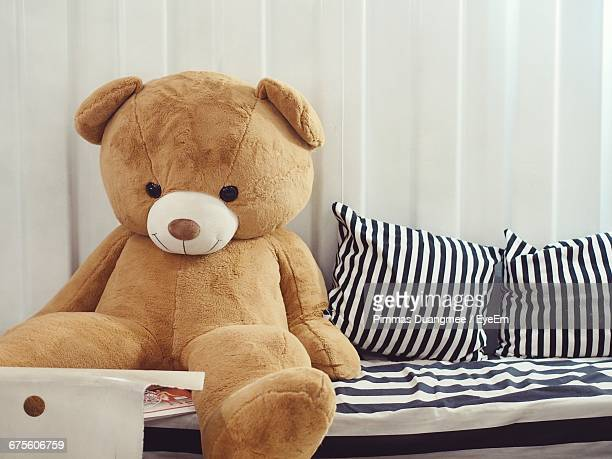 Teddy Bear By Cushions On Bed At Home