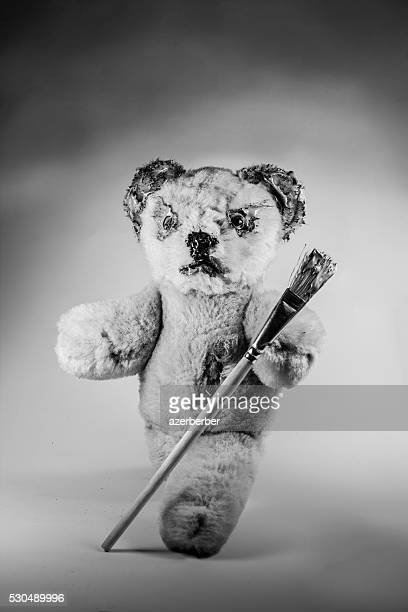 Black and white photo of teddy bear holding a paintbrush