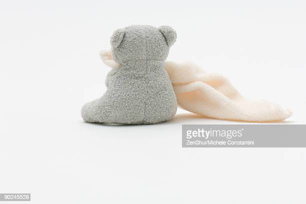 Teddy bear holding blanket, rear view