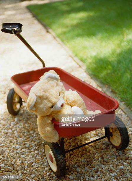 teddy bear in a red wagon - toy wagon stock photos and pictures