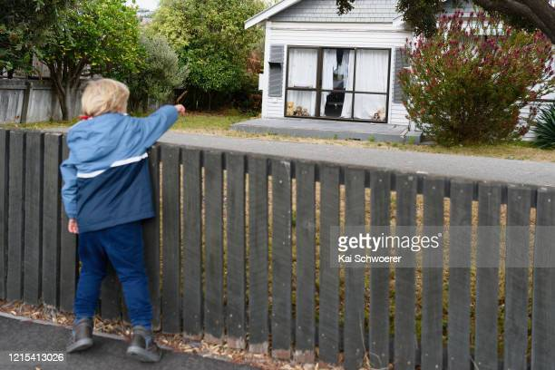Teddy bear is seen in a window as a boy, who is the photographer's son, passes by on March 29, 2020 in Christchurch, New Zealand. Inspired by the...