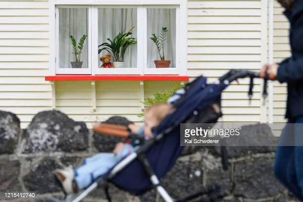 Teddy bear is seen in a window as a child in a pram passes by on March 29, 2020 in Christchurch, New Zealand. Inspired by the Michael Rosen...