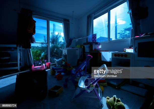 A teddy bear lies among other things in the children's room of a house on October 5 2017 in Futaba Fukushima Japan A full moon lights up the sky...