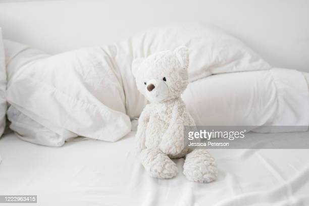 teddy bear on bed - ぬいぐるみ ストックフォトと画像