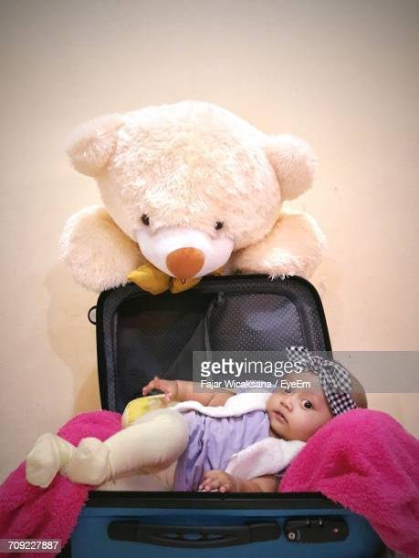 Teddy Bear Over Baby Girl Lying In Suitcase Against Wall
