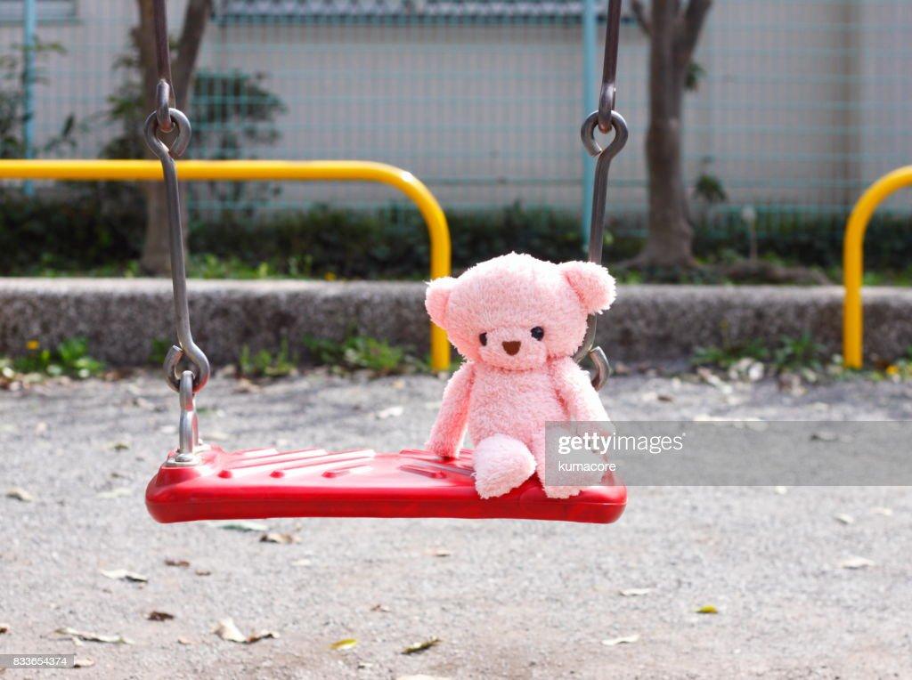 Teddy bear sit on a swing : Stock Photo