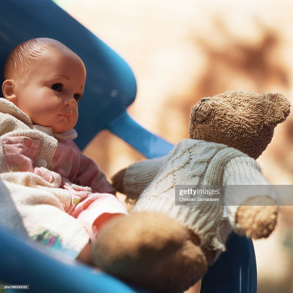 Teddy bear sitting in chair with baby doll. : Stockfoto