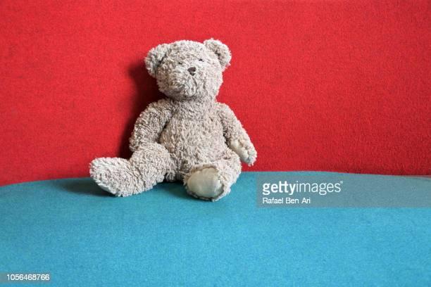 teddy bear sitting on a couch - rafael ben ari stockfoto's en -beelden