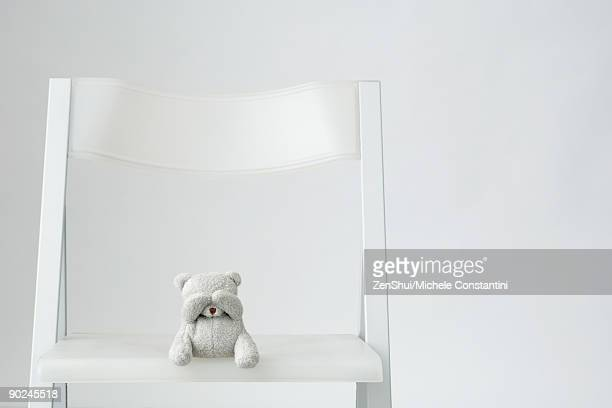 Teddy bear sitting on over-sized chair, covering eyes