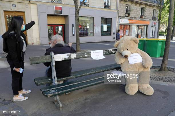 Teddy bear wearing a sign reading people to obey social distancing is seen on a bench in the 'Les Gobelins' area on April 15, 2020 in Paris, France....