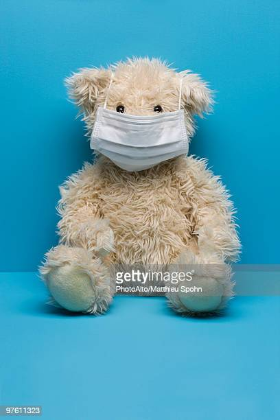 teddy bear wearing flu mask - flu mask stock photos and pictures