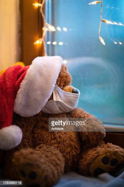 teddy bear wearing protective medical mask on quarantine or self-isolation on christmas - father christmas stock pictures, royalty-free photos & images