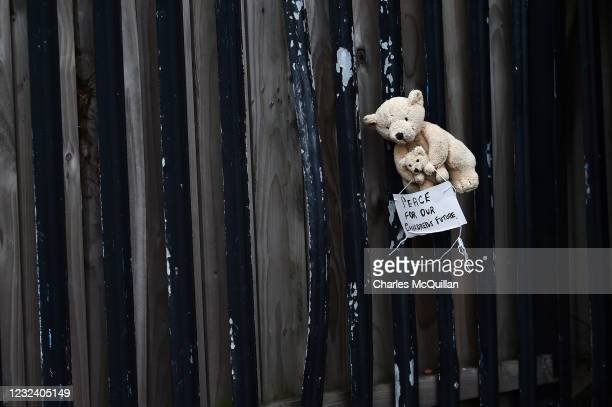 Teddy bear with a note on which reads 'Peace for our children's future' is hung on a railing near the 'Peace Gates' interface on April 19, 2021 in...