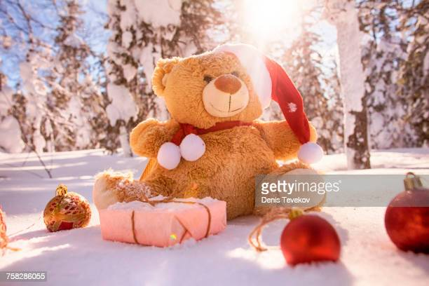 Teddy bear with Christmas gifts and ornaments in snow