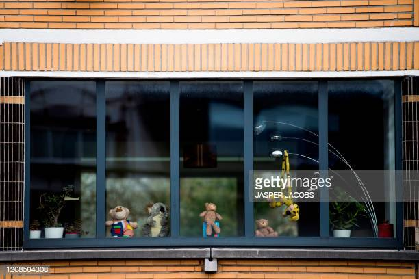 Teddy bears are placed on a windowsill of a home in Mechelen on March 29 as a new game for children who are passing by during outside walks can look...