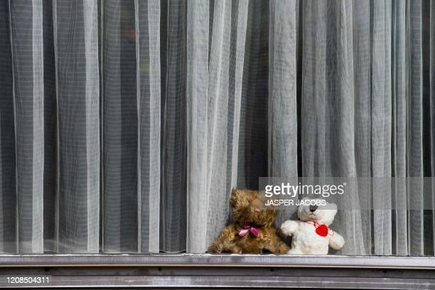 Teddy bears are placed on a windowsill of a home in Mechelen on March 29 as a new game for children who are passing by during outside walks, can look...