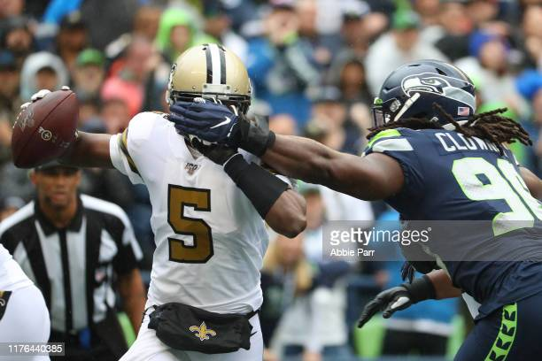 Teddy Bridgewater of the New Orleans Saints attempts to avoid a tackle by Jadeveon Clowney of the Seattle Seahawks in the first quarter during their...