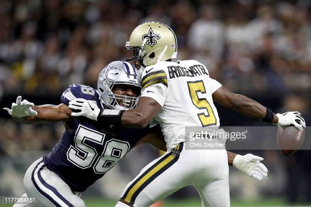 Teddy Bridgewater of the New Orleans Saints gets tackled by Robert Quinn of the Dallas Cowboys during the second quarter in the game at Mercedes Benz...