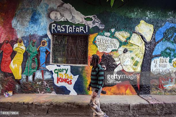 Teddy Dan a Rastafarian artist and musician originally from Jamaica walks next to artwork on the wall of his house on January 26 2017 in Shashamene...