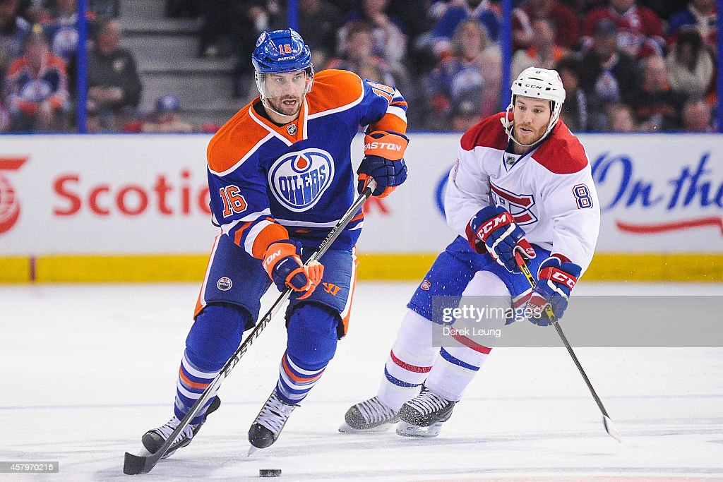 Teddy Purcell #16 of the Edmonton Oilers skates with the puck past Brandon Prust #8 of the Montreal Canadiens during an NHL game at Rexall Place on October 27, 2014 in Edmonton, Alberta, Canada. The Oilers defeated the Canadiens 3-0.