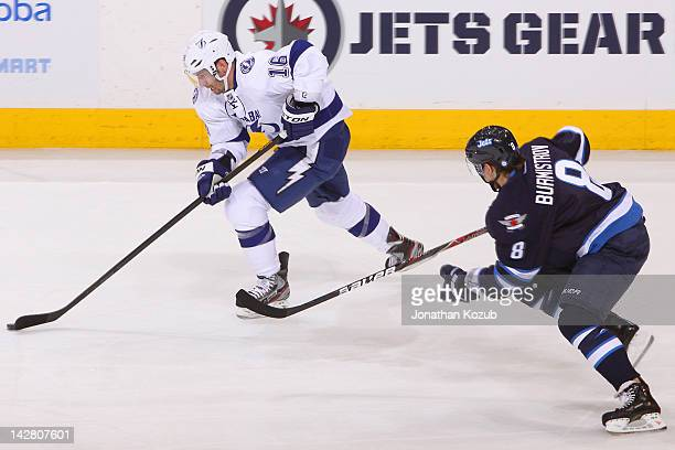 Teddy Purcell of the Tampa Bay Lightning carries the puck up the ice as Alexander Burmistrov of the Winnipeg Jets gives chase during first period...