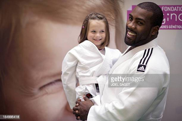 Teddy Riner French judo's champion and godfather of the foundation 'Imagine' which supports children with genetic diseases poses with a child during...