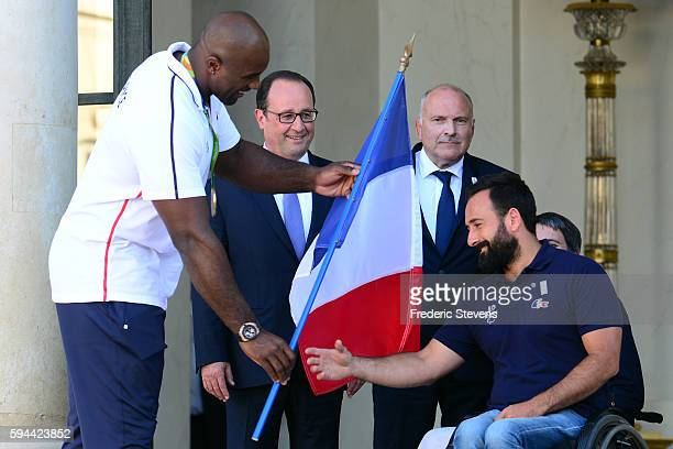 Teddy Riner judo Gold medalist gives the French flag to Michael Jeremiasz for the Paralympic Games in Rio in the presence of French President...