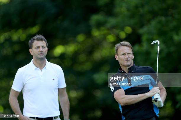 Teddy Sheringham of England the former football player plays a shot watched by Tim Sherwood during the proam for the 2017 BMW PGA Championship on the...