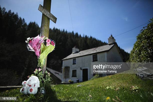 A teddybear and floral tributes adorn a post outside of the former home of defendant Mark Bridger in Ceinws Mid Wales who is currently on trial for...