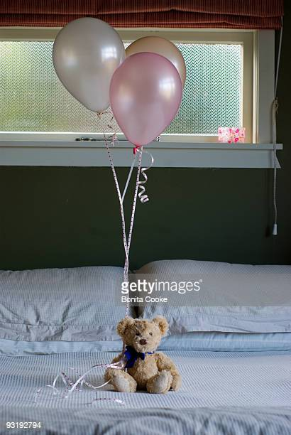 teddybear holding balloons.  - tied to bed stock pictures, royalty-free photos & images