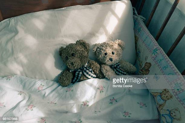 teddybears in a cot bed - empty crib stock photos and pictures
