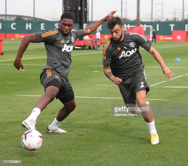 Teden Mengi and Bruno Fernandes of Manchester United in action during a first team training session at Aon Training Complex on September 15 2020 in...