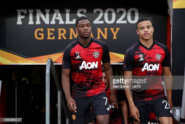Teden Mengi and Mason Greenwood of Manchester United walk out to warm up prior to the UEFA Europa League Quarter Final between Manchester United and...