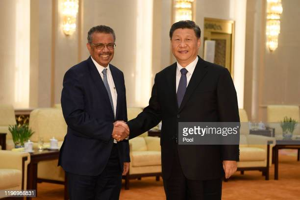 Tedros Adhanom Director General of the World Health Organization shakes hands with Chinese President Xi Jinping before a meeting at the Great Hall of...