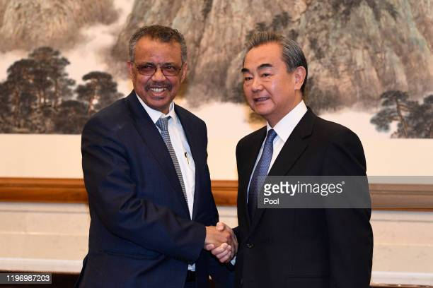 Tedros Adhanom Director General of the World Health Organization shakes hands with Chinese State Councilor and Foreign Minister Wang Yi before a...