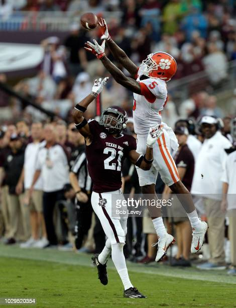 Tee Higgins of the Clemson Tigers leaps over Charles Oliver of the Texas A&M Aggies to make a catch and runs for a 64 yard touchdown in the second...